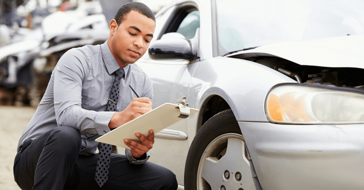 man-inspecting-car-damage
